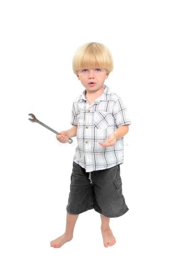Geïsoleerdr schot van het jonge jongen spelen met grote moersleutel stock afbeelding