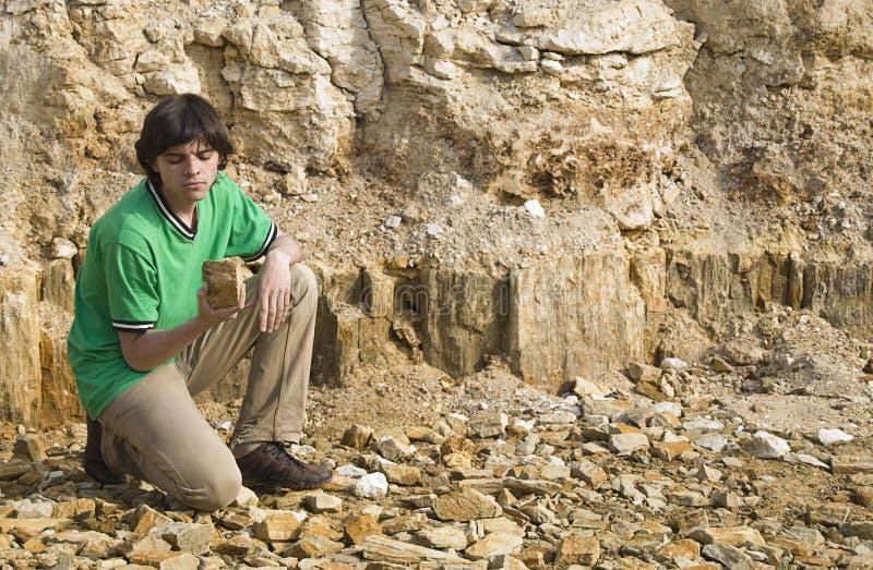 Geólogo joven que estudia el tipo de la roca foto de archivo libre de regalías