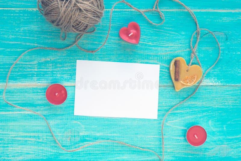 Geöffnete leere Grußkarte auf einem blauen hölzernen schäbigen Hintergrund mit Herzen, Kerzen und einem Strang des Threads Modell stockbilder