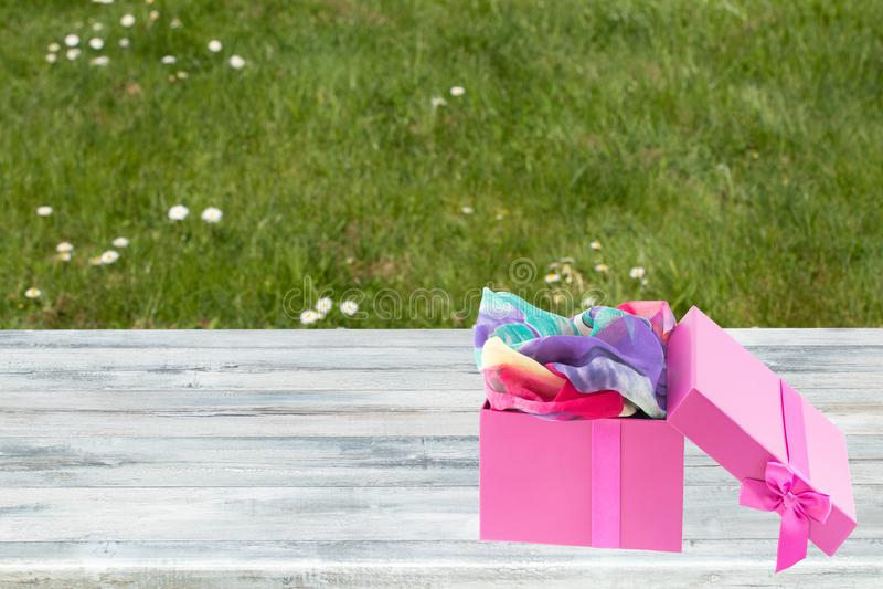 Geöffnete purpurrote Geschenkbox mit buntem Schal nach innen auf rustikaler heller Tabelle mit grünem backround Raum für Text ode stockbilder