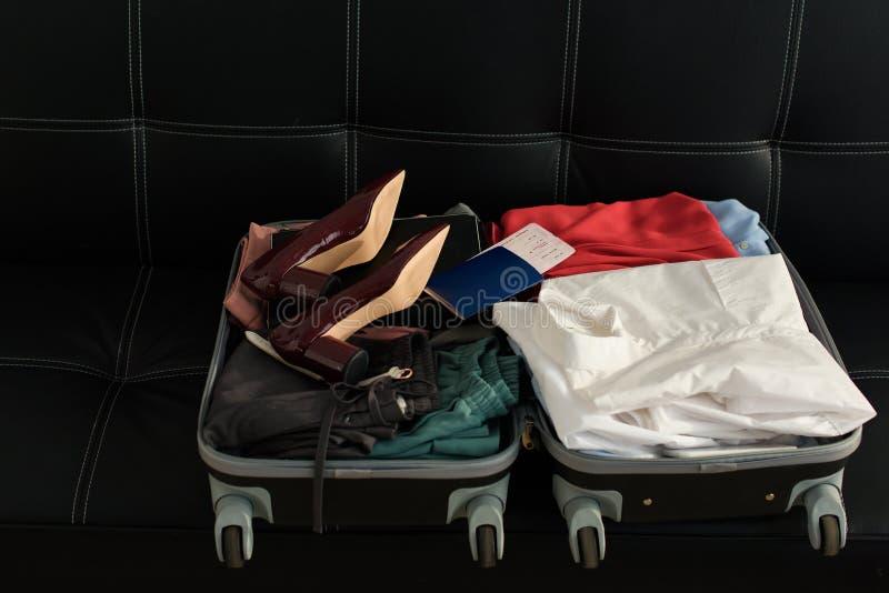 geöffnete Reisetasche mit Pass, Kleidung und Fersen lizenzfreie stockfotos
