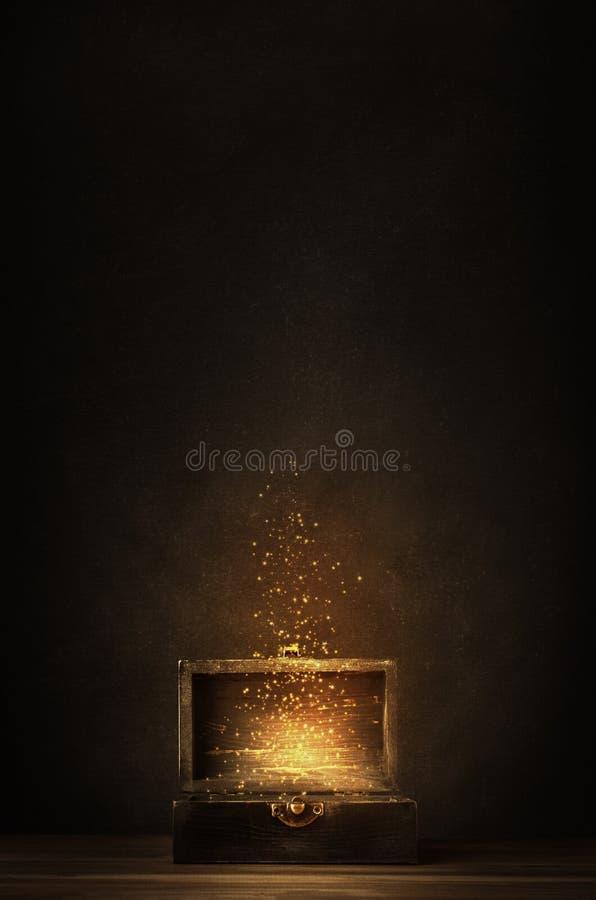 Geöffnete Schatztruhe, die glühende Scheine und Sterne freigibt lizenzfreies stockbild
