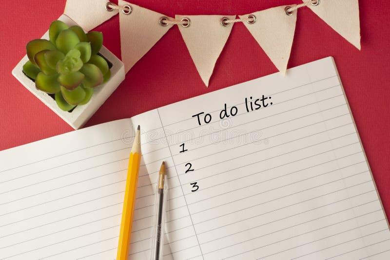 Geöffneter Organisator mit a, zum der Listenaufschrift, weiße Seiten des leeren Papiers zu tun Arbeitstabelle mit dekorativem saf stockfotografie