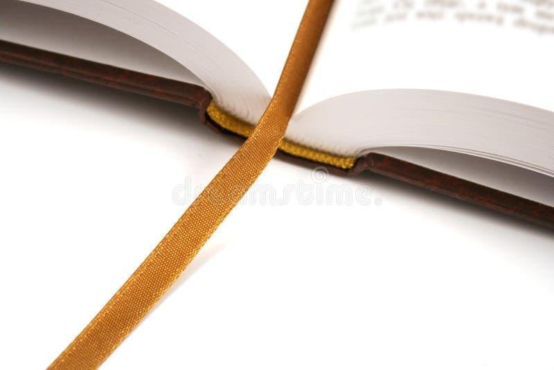 Geöffnetes Buch mit goldenem Bookmark lizenzfreie stockfotografie