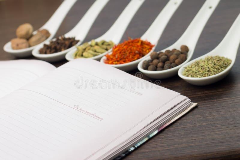 Geöffnetes Küchenbuch mit verschiedenem von den Gewürzen stockbild
