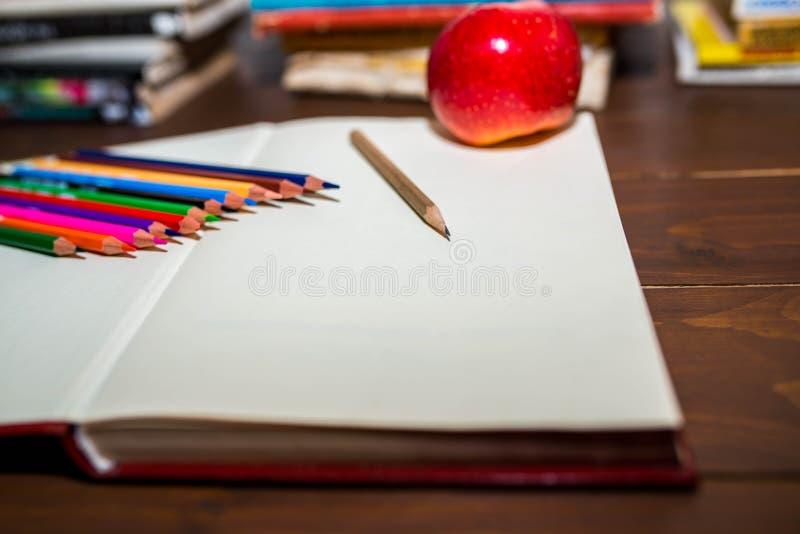 Geöffnetes leeres Notizbuch, Apfel, Farbbleistifte, bunte Bücher im Hintergrund lizenzfreie stockfotos