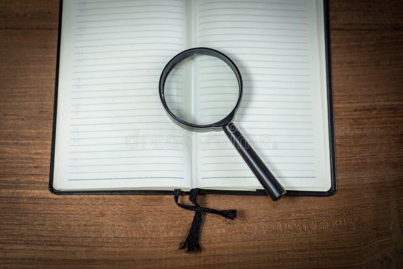 Geöffnetes leeres Notizbuch mit Lupe lizenzfreie stockfotografie