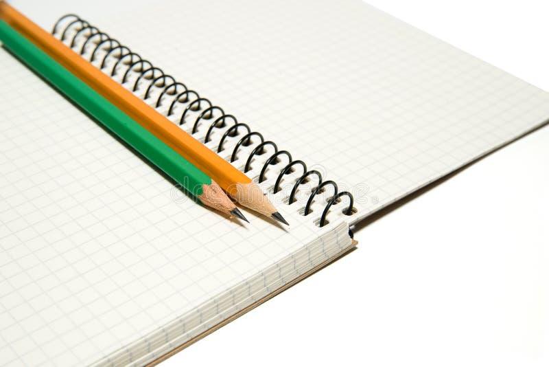 Geöffnetes Notizbuch und Bleistifte an über Weiß lizenzfreie stockfotos