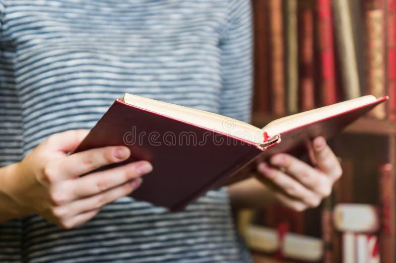 Geöffnetes rotes Abdeckungsbuch in den Händen des Mannes Weicher Fokus lizenzfreies stockfoto