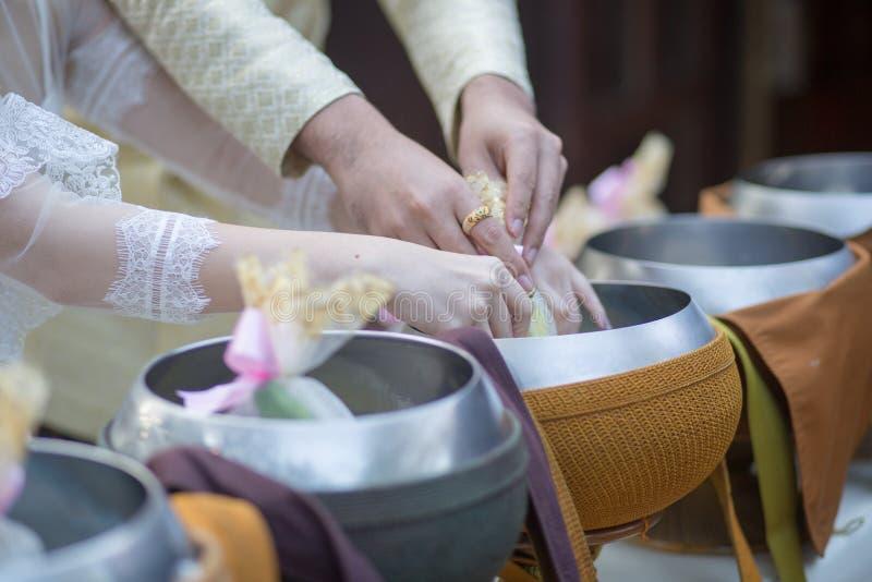Ge allmosamat i traditionellt thailändskt bröllop royaltyfria foton
