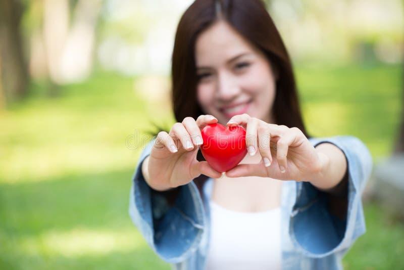 Ge begrepp för förälskelse tillsammans: Röd hjärta för gullig asiatisk kvinnahåll royaltyfri fotografi