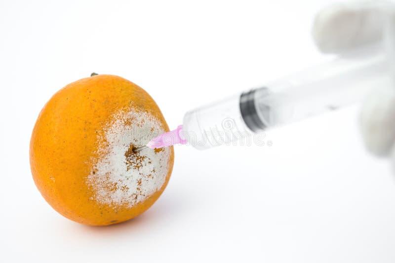 Ge en injektion till en rutten apelsin på vit arkivbild