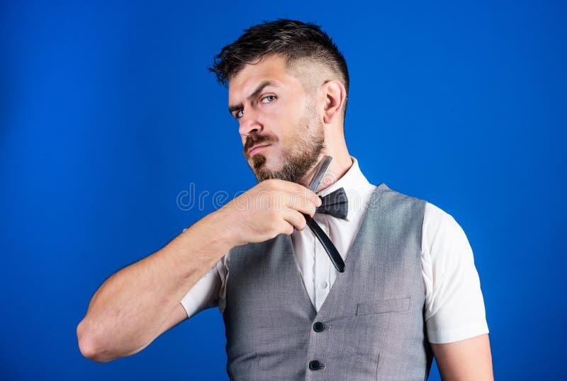 Ge en ren rakning Barberare med tappningbarberarehjälpmedlet Rakknivbarberaren shoppar Skäggig man med den raka rakkniven brutal  arkivbild