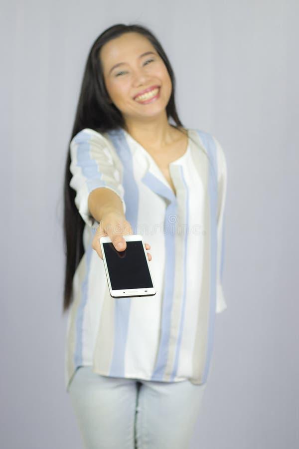 Ge en smart telefon till dig, le kvinnainnehavmobiltelefonen Isolerat p? gr? bakgrund arkivbild