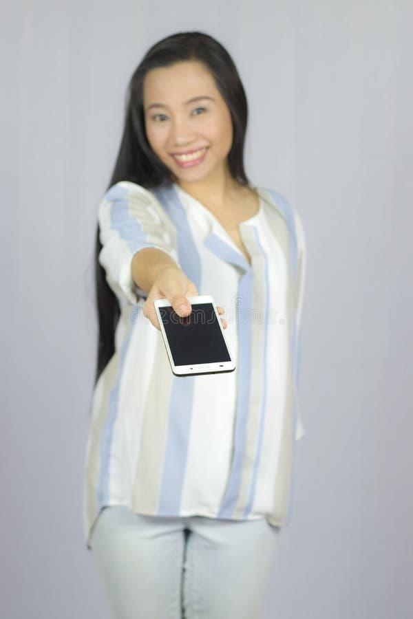 Ge en smart telefon till dig, le kvinnainnehavmobiltelefonen Isolerat p? gr? bakgrund royaltyfri fotografi