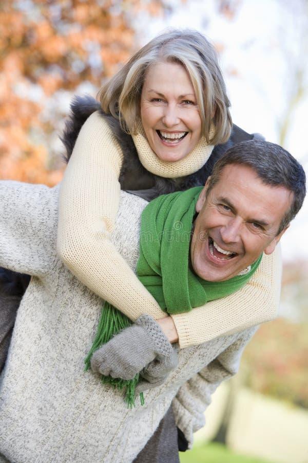 ge för rittpensionär för man på ryggen kvinnan royaltyfri foto