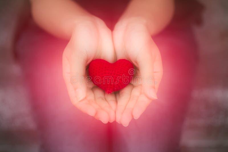 ge hj?rta röd förälskelsehjärta för closeup i tonårig hand för flicka royaltyfri fotografi