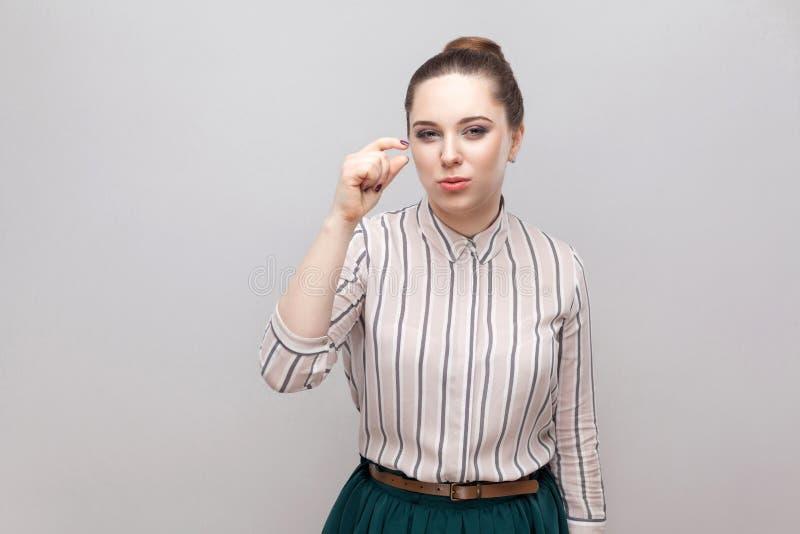 Ge mig lite grann behar mer Stående av den hoppfulla härliga unga kvinnan i randig skjorta med makeup och samlat förbud arkivfoto