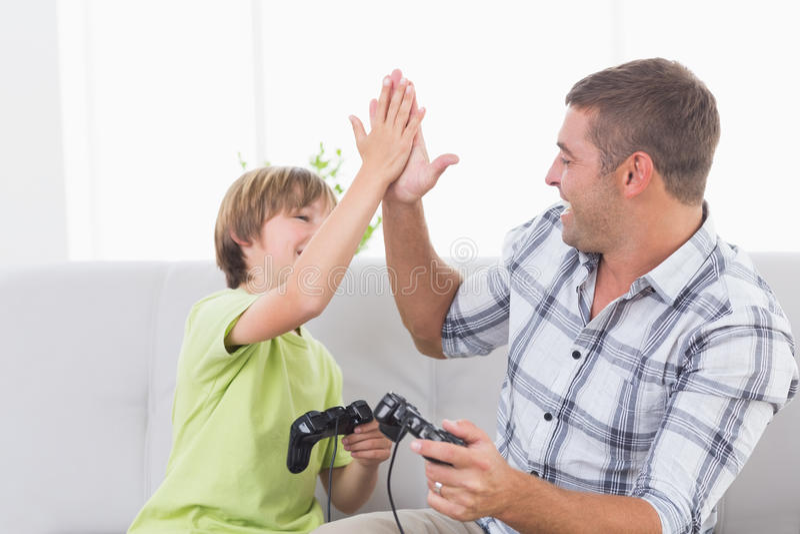 Ge sig för fader som och för son är högt-fem, medan spela videospelet royaltyfri foto