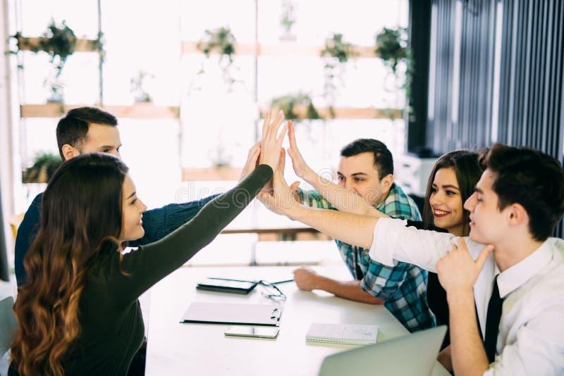 Ge sig för fotoredaktörer som är högt-fem i mötesrum på det idérika kontoret royaltyfri fotografi