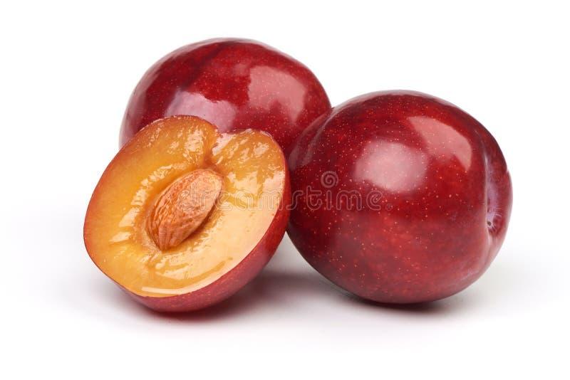 Ge?soleerde pruimen Anderhalf van rood die pruimfruit met bladeren op witte achtergrond worden geïsoleerd stock fotografie