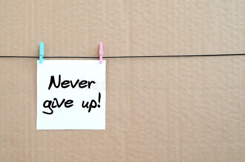 Ge upp aldrig! Anmärkningen är skriftlig på en vit klistermärke den hängningintelligens royaltyfri bild
