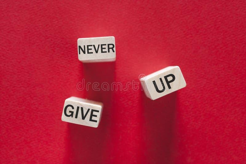Ge upp aldrig det motivational meddelandet arkivfoton