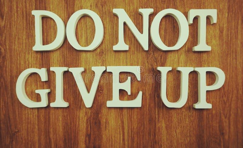 Ge upp inte ordet som göras från träkuber med bokstavsalfabet på träbakgrund royaltyfri fotografi