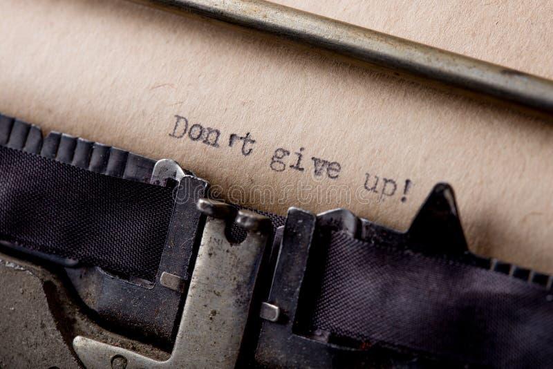 Ge upp inte - textmeddelandet på skrivmaskinsnärbilden arkivfoton