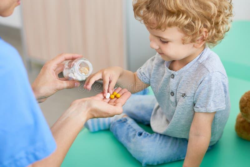 Ge vitaminer till den lockiga lilla patienten arkivbild
