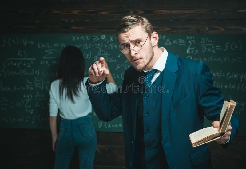 Geageerde jonge professor die passionately wiskundige formule verklaren Knappe leraar die een boek houden terwijl het geven van a stock afbeeldingen