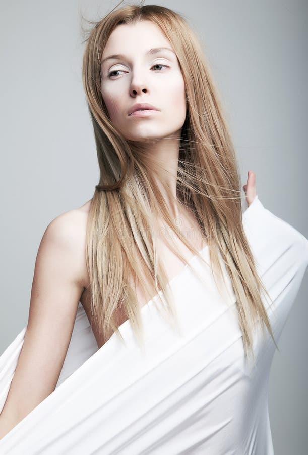Gealarmeerd zacht helft-gekleed meisje in witte kleren stock foto