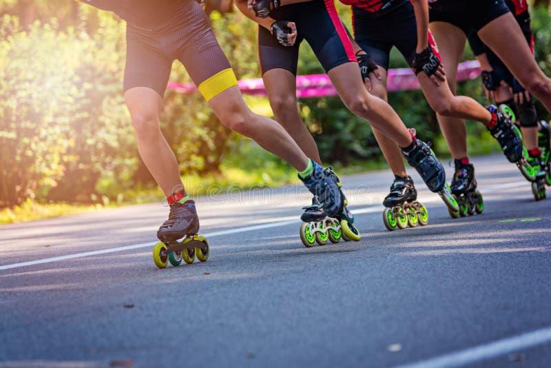 Gealigneerde rolschaatsers die in het park o rennen stock afbeeldingen