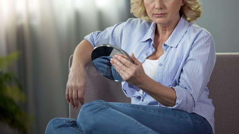 Gealterte blonde Dame, die ihr Gesicht untersucht einen Handspiegel, Alterungsprozess berührt stockbild