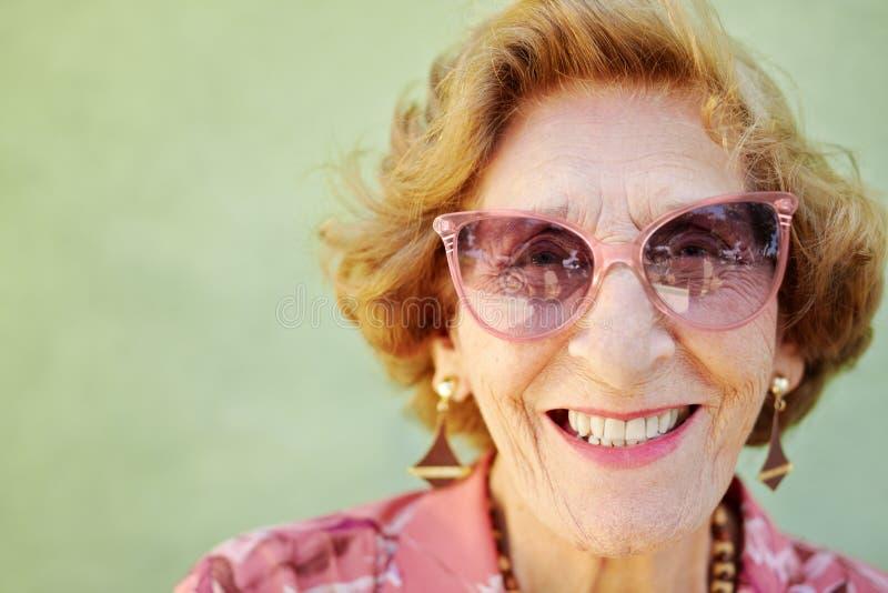 Gealterte Frau mit rosafarbenen Brillen lächelnd an der Kamera stockfotos