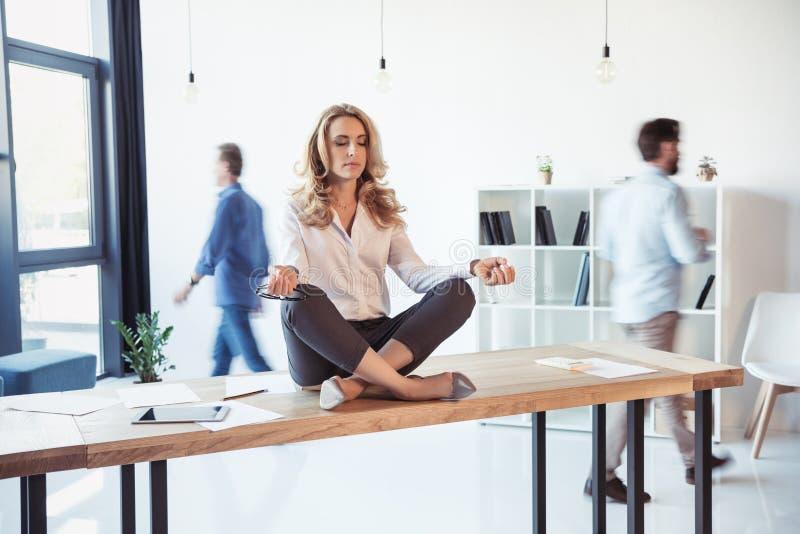 Gealterte Geschäftsfrau, die auf Tabelle sitzt und in Lotussitz während Kollegen hinten arbeiten meditiert stockfoto