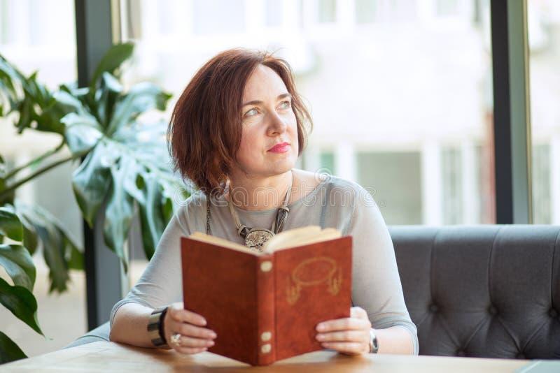 Gealterte stilvolle Frau mit einem Buch träumend lizenzfreie stockbilder