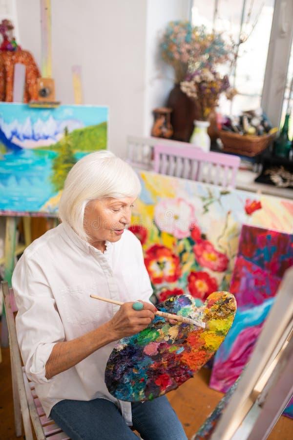 Gealterter begabter und berühmter Künstler, der nahe Segeltuch und dem Arbeiten sitzt stockbild