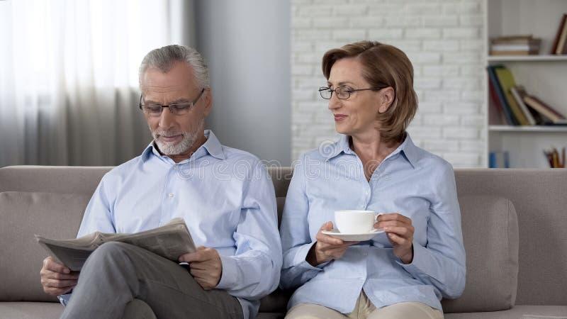 Gealterter Ehemann und Frau, die auf Sofa, Mannlesezeitung, trinkender Tee der Frau sitzt lizenzfreie stockfotos