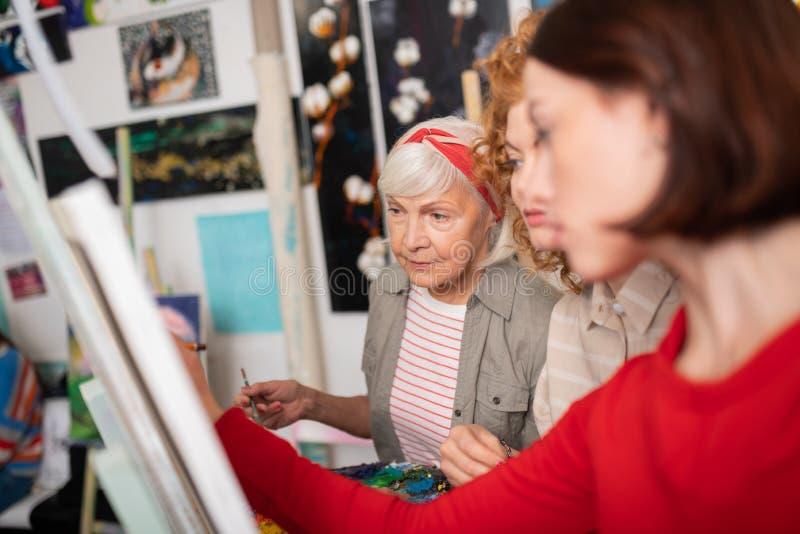 Gealterter grau-haariger Künstler, der Arbeiten ihrer Studenten betrachtet lizenzfreie stockfotos