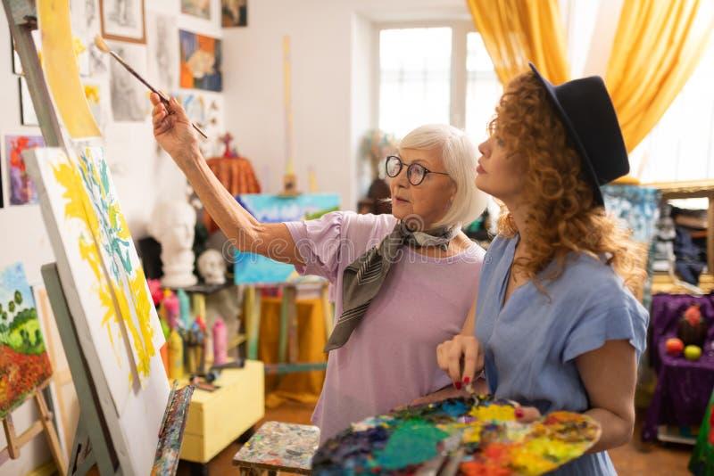 Gealterter grau-haariger Kunstlehrer in den Gläsern sprechend mit ihrem Studenten lizenzfreie stockfotografie