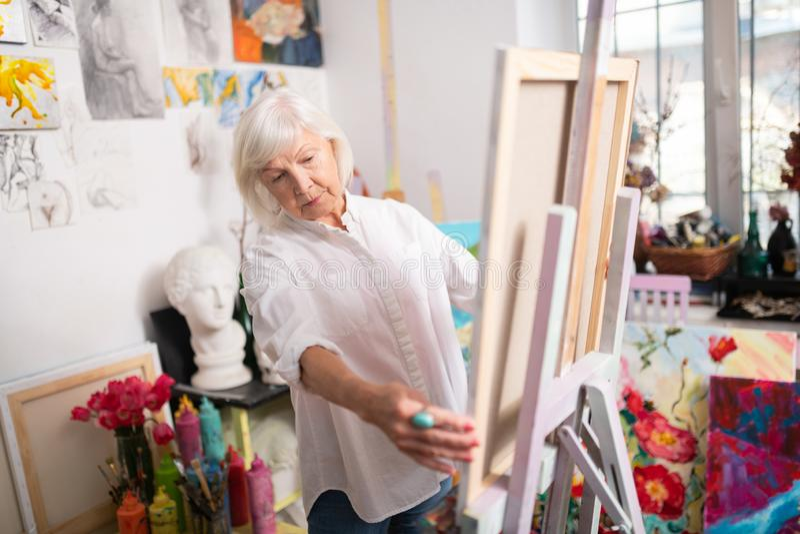 Gealterter Künstler mit kurzer Stellung des blonden Haares nahe zeichnendem Gestell stockbilder