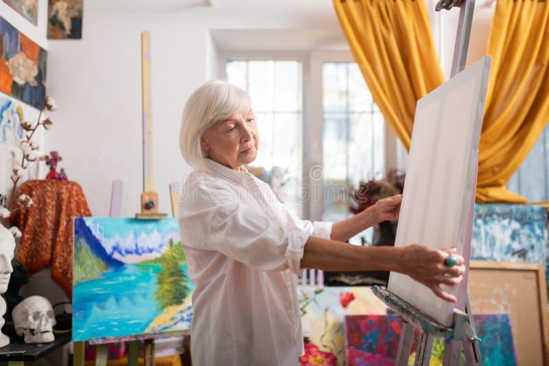 Gealterter Künstler mit Pendelschnittgefühl angespornt vor Malerei lizenzfreie stockfotografie