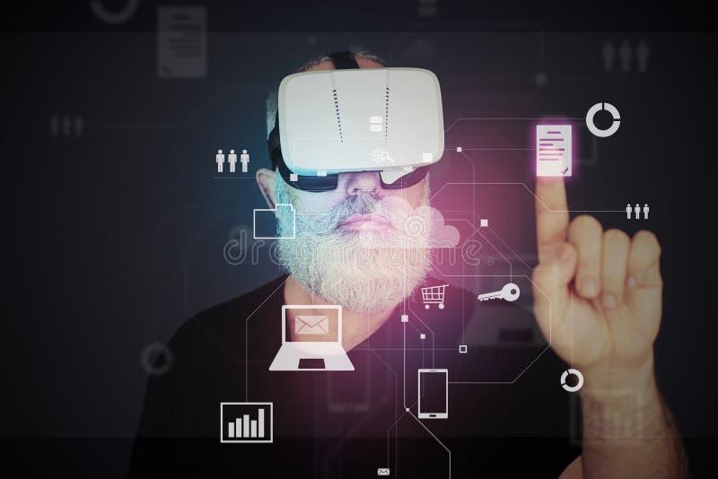 Gealterter Mann in den Gläsern der virtuellen Realität, die auf virtuelle Ikone klicken stockfotografie