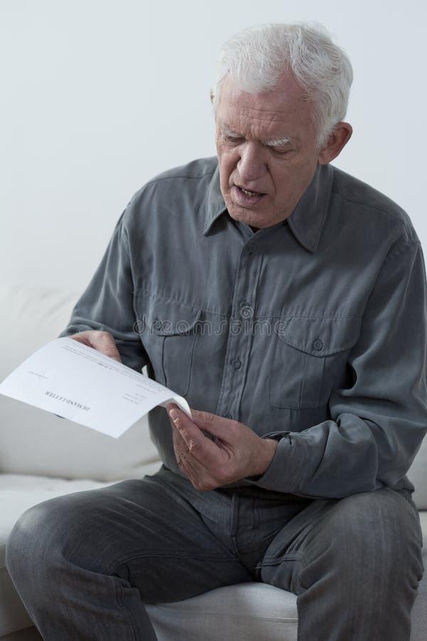 Gealterter Mann, der unbezahlte Rechnung liest lizenzfreie stockfotos