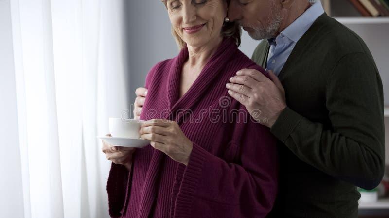 Gealtertes trinkendes bereitstehendes Fenster Tees Dame, Mann, der geliebte Frau umarmt und küsst lizenzfreie stockfotografie