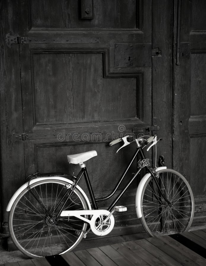 Gealtertes Weinleseschwarzfahrrad, große hölzerne Tür, schwarz stockfotografie
