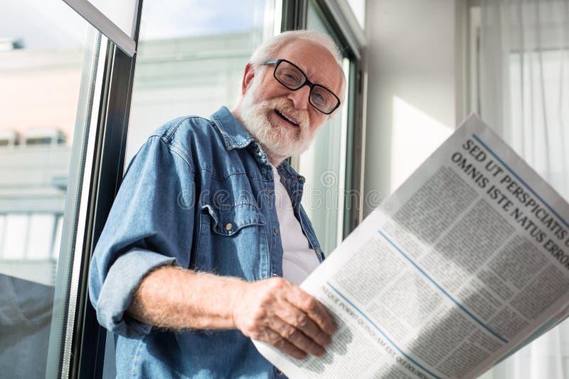 Geamuseerde vrolijke mens die camera bekijken terwijl het lezen van document stock foto's