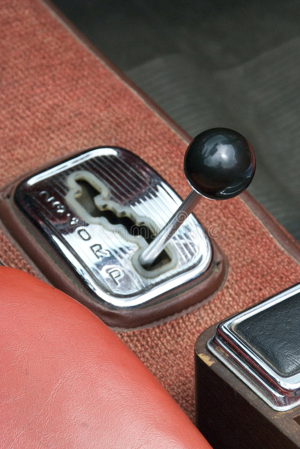 Gear lever. A automatic shift car gear lever of a old red car stock photos