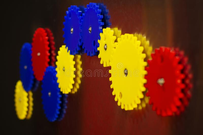 Gear mechanism for logical development of children on a magnet of different colors-red, blue, yellow royalty free stock photos